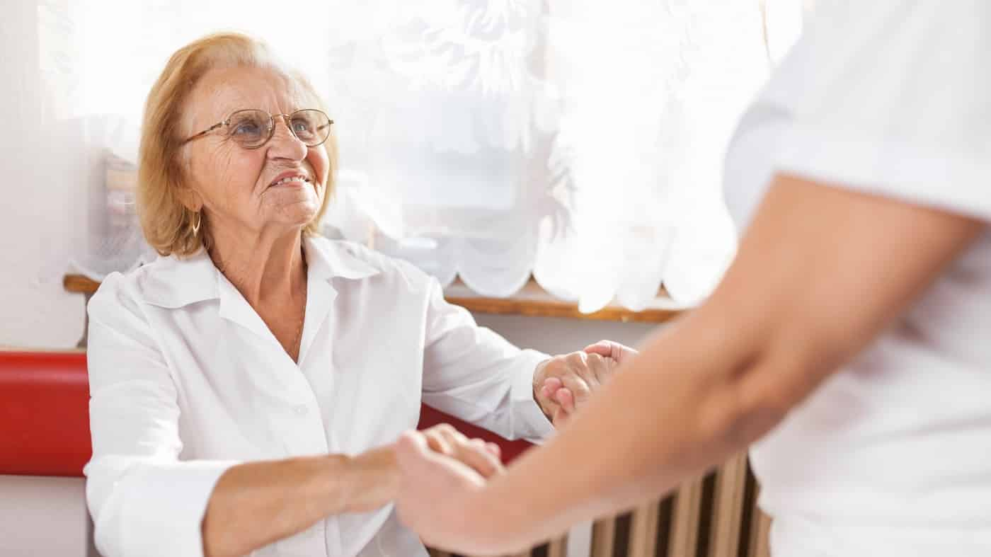older lady being held by hands from nurse